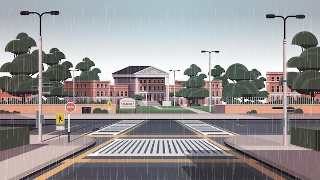 Schoolgebouw lege voortuin met weg zebrapad stadsgezicht achtergrond
