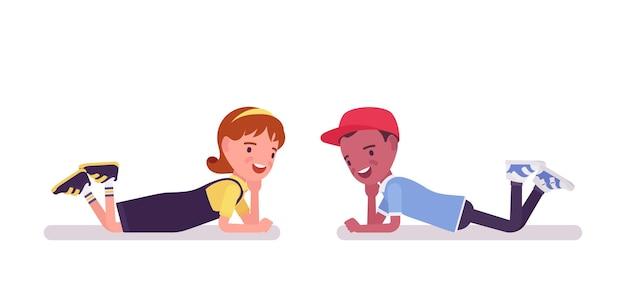 Schooljongen en meisje hebben plezier, liggend op de buik