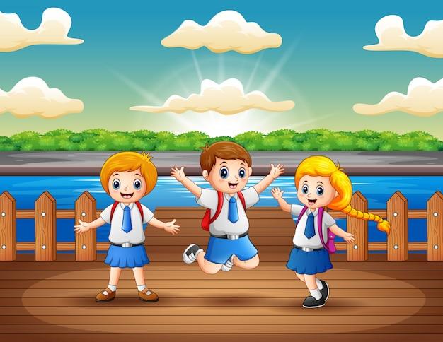 Schoolkinderen die pret hebben bij de houten pijler