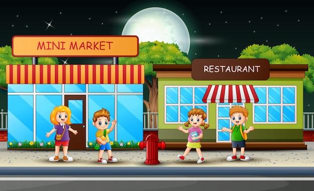 Schoolkinderen lopen langs de mini-markt en het restaurant