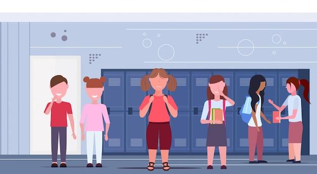 Schoolmeisje gepest door andere leerlingen groep zwaarlijvigheid concept vrienden pesten verdrietig overgewicht meisje in school gang interieur vlak horizontaal volledige lengte