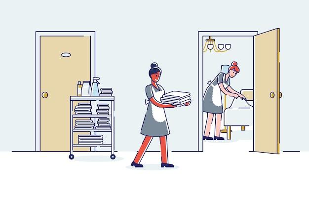 Schoonmaakkamer van het hotelroomserviceteam: vrouwelijke dienstmeisjes brengen nieuwe handdoeken en bed opmaken.