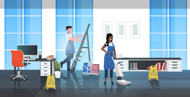 Schoonmakers paar met behulp van stofzuiger en ladder afro-amerikaanse conciërges team in uniform samen te werken schoonmaak concept moderne kantoor interieur horizontale volledige lengte