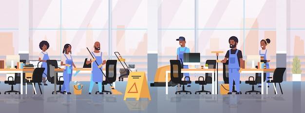 Schoonmakers team in uniform samenwerken schoonmaak service concept conciërges met behulp van professionele apparatuur moderne co-working open ruimte kantoor interieur volledige lengte horizontaal