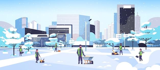 Schoonmakers team met behulp van verschillende apparatuur en gereedschappen sneeuwruimen concept mannen vrouwen in uniform schoonmaken winter besneeuwde park stadsgezicht platte volledige lengte horizontale vector illustratie