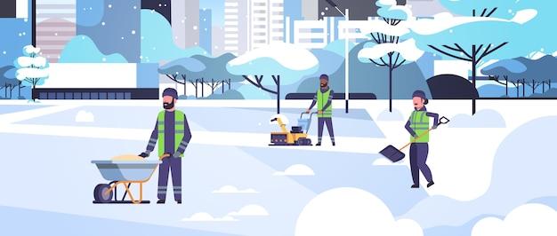 Schoonmakers team met behulp van verschillende apparatuur en gereedschappen sneeuwruimen concept mix race mannen vrouwen in uniform schoonmaken winter besneeuwde park stadsgezicht plat volledige lengte horizontale vector illustratie