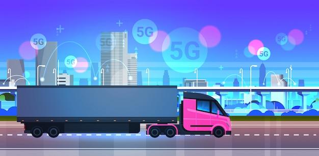 Semi vrachtwagenaanhangwagen het drijven stadsweg 5g het online draadloze concept van de systeemverbinding modern stadsgezicht achtergrond snel logistiek logistiek vervoer horizontaal