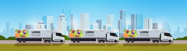 Semi vrachtwagenaanhangwagen met organische groenten op van de het veganistvoedsel van de stadsweg natuurlijk veganistisch voertuig van de de leveringsdienst van het stadsvoedsel met verse groentencityscape horizontale exemplaarruimte als achtergrond