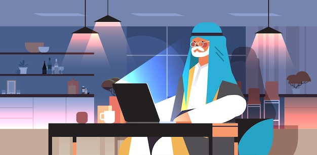 Senior arabische zakenman freelancer werkt aan laptop arabische man zit op de werkplek in de donkere nacht thuiskamer