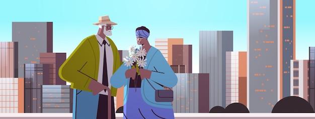 Senior koppel met bloemen met een date afro-amerikaanse grootouders die samen tijd doorbrengen met stadsgezicht achtergrond