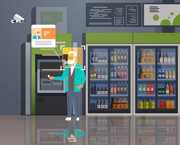 Senior man geld opnemen atm geldautomaat identificatie bewaking cctv gezichtsherkenning moderne grosery winkel supermarkt interieur bewakingscamera systeem