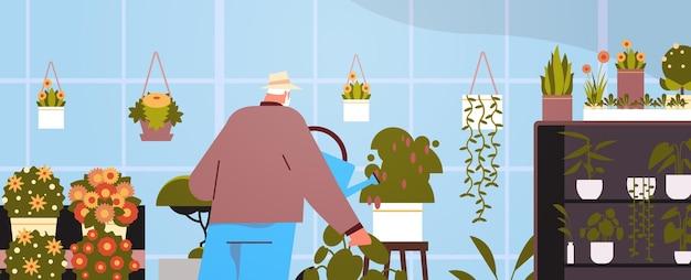 Senior man tuinman met gieter die zorgt voor potplanten in huis, tuin, woonkamer of kantoorinterieur
