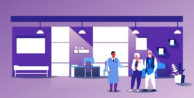 Senior paar een bezoek aan vrouwelijke arts het geven van medische raadpleging en recept voor volwassen man vrouw patiënten gezondheidszorg concept modern ziekenhuis kantoor interieur