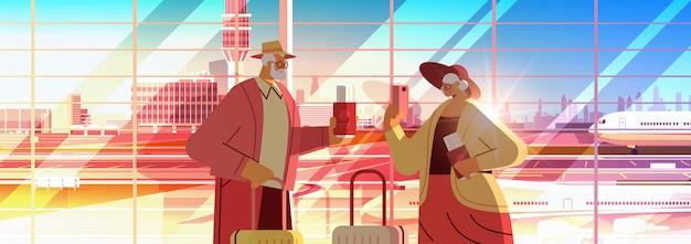 Senior paar toeristen die smartphones gebruiken, grootouders met bagagepaspoorten en tickets klaar om in te stappen