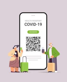 Senior reizigers die digitaal immuniteitspaspoort gebruiken met qr-code op smartphonescherm, risicovrij covid-19 pandemie