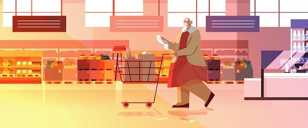 Senior vrouw met vol producten trolley kar controleren boodschappenlijstje in supermarkt moderne kruidenierswinkel interieur