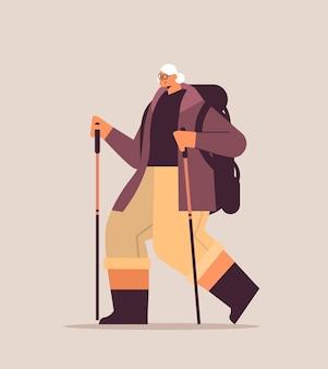 Senior vrouw wandelaar reizen met rugzak en stokken voor wandelen nordic walking actief ouderdomsconcept