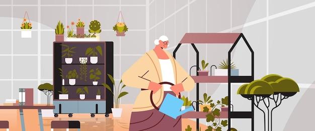 Senior vrouwelijke tuinman met gieter die zorgt voor potplanten in de huistuin, woonkamer of kantoorinterieur