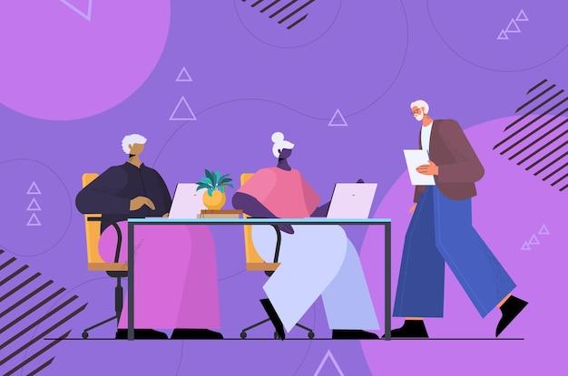 Senior zakenmensenteam dat digitale gadgets gebruikt oude zakenmensen die op laptops op de werkplek werken