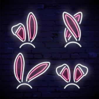 Set roze en witte neon konijn oren geïsoleerd op donkere bakstenen achtergrond.
