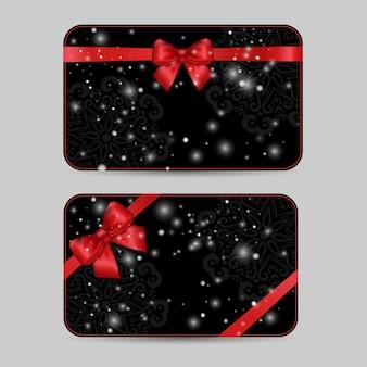 Set van decoratieve kaartsjablonen met glanzende vakantie rode satijnen lint strik op donkere zwarte kanten achtergrond met sneeuw.
