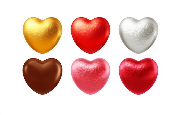 Set van realistische hartvormige chocolaatjes verpakt in een folie snoeppapiertje.