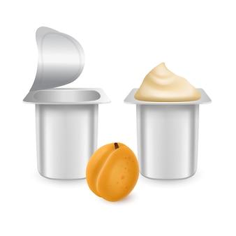 Set van witte matte plastic potten voor yoghurtcrème dessert of jam verpakking sjabloon yoghurtroom met verse abrikozen geïsoleerd