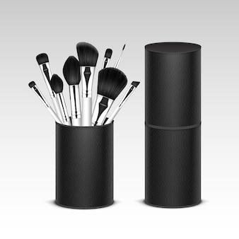 Set van zwarte schone professionele make-up concealer poeder blozen oogschaduw wenkbrauwborstels met witte handgrepen in zwart lederen buis geïsoleerd op witte achtergrond