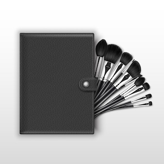 Set van zwarte schone professionele make-up concealer poeder blozen oogschaduw wenkbrauwborstels met zwarte handgrepen en lederen tas geïsoleerd op witte achtergrond