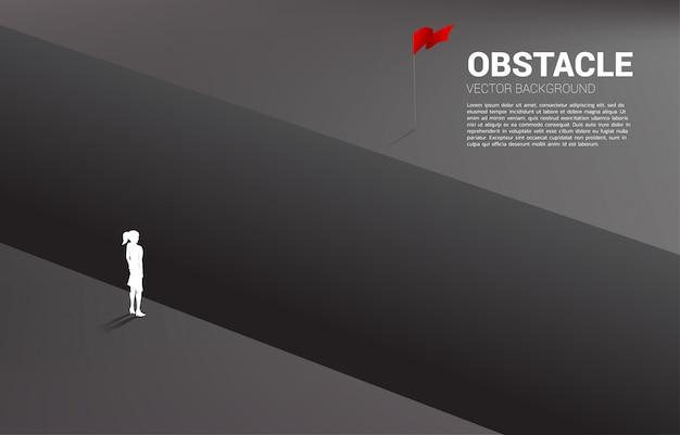 Silhouet dat van onderneemster zich bij kloof bevindt die aan doel kijkt.