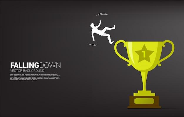 Silhouet dat van zakenman van trofee valt.