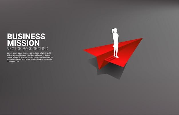 Silhouet die van onderneemster zich op rood origamidocument vliegtuig bevinden. businessconcept van leiderschap, startend bedrijf en ondernemer
