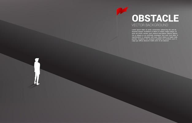 Silhouet die van zakenman zich bij kloof bevinden die aan doel kijken