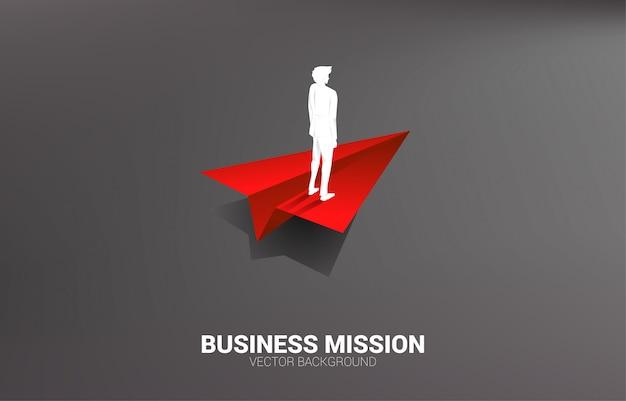 Silhouet die van zakenman zich op rood origamidocument vliegtuig bevinden. businessconcept van leiderschap, startend bedrijf en ondernemer