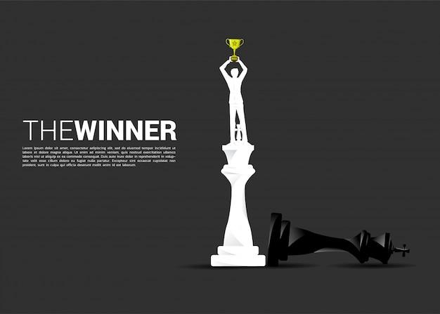 Silhouet die van zakenman zich op winnaarsschaak bevinden aan schaakmat.