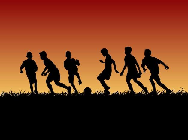 Silhouet groep van voetbal jongen op zonsondergang