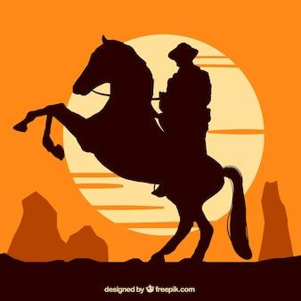 Silhouet van cowboy die bij zonsondergang berijdt