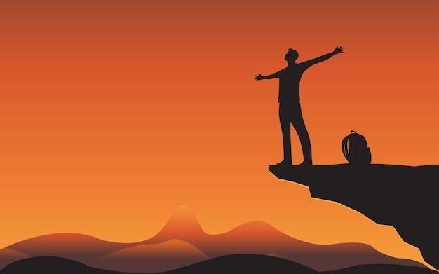 Silhouet van de mens die zich op bergklif ontspant