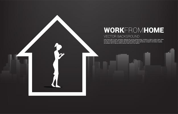 Silhouet van de mobiele telefoon van het vrouwengebruik in huis met stadsachtergrond. concept voor thuiswerken op afstand en techniek.