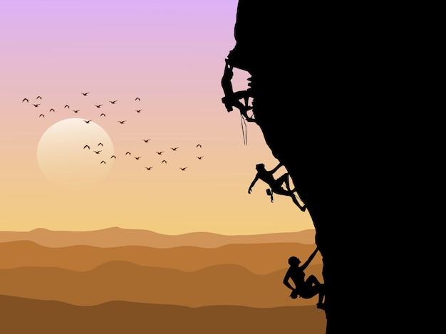 Silhouet van drie bergbeklimmers klimmen met zonsondergang op de achtergrond.