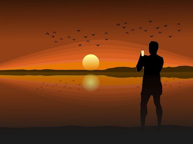 Silhouet van een man die een mobiele telefoon vasthoudt om een zonsondergangfoto te maken