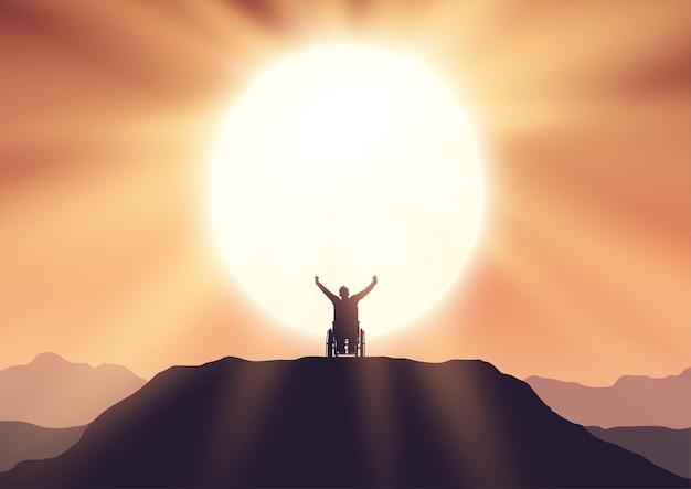 Silhouet van een man in een rolstoel bovenop een heuvel, hand in hand in de lucht met vreugde