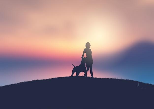Silhouet van een vrouw en haar hond tegen een zonsondergang landschap