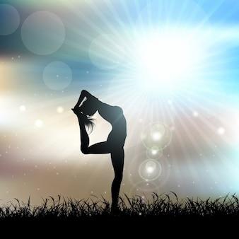 Silhouet van een vrouw in een yoga houding in een zonnig landschap