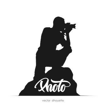 Silhouet van fotograaf zittend op steen geïsoleerd op een witte achtergrond.