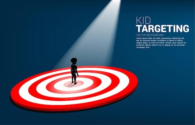Silhouet van jongen die zich op centrum van dartbord met vleklicht bevindt. zakelijke illustratie van kid marketing doel en klant.