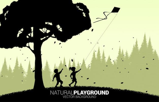 Silhouet van jongen en meisje die met vliegende vlieger in de hemel lopen