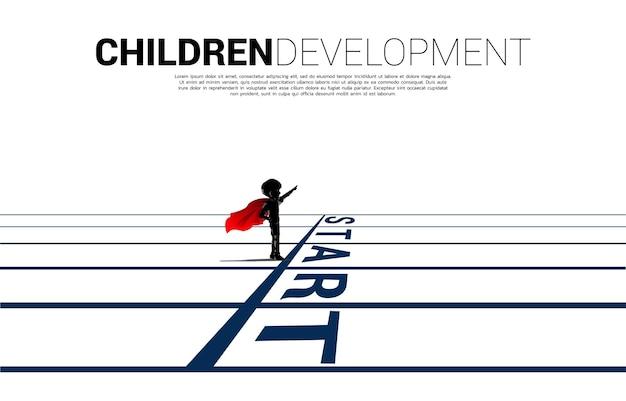 Silhouet van jongen in superheldenkostuum die zich bij de startlijn bevindt. concept van onderwijs start en toekomst van kinderen.