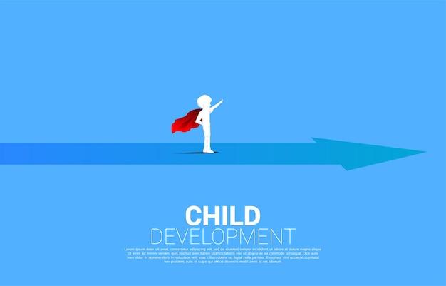 Silhouet van jongen in superheldenkostuum die zich op pijl bevindt. concept van onderwijs start en toekomst van kinderen.