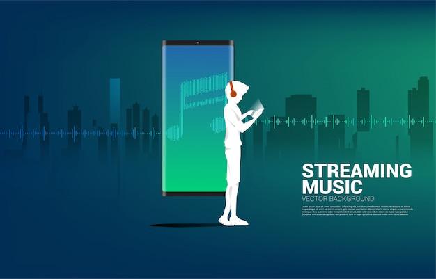 Silhouet van man met hoofdtelefoon en geluidsgolf muziek equalizer achtergrond.
